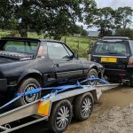 Fiat X1/9 on trailer behind a Land Rover