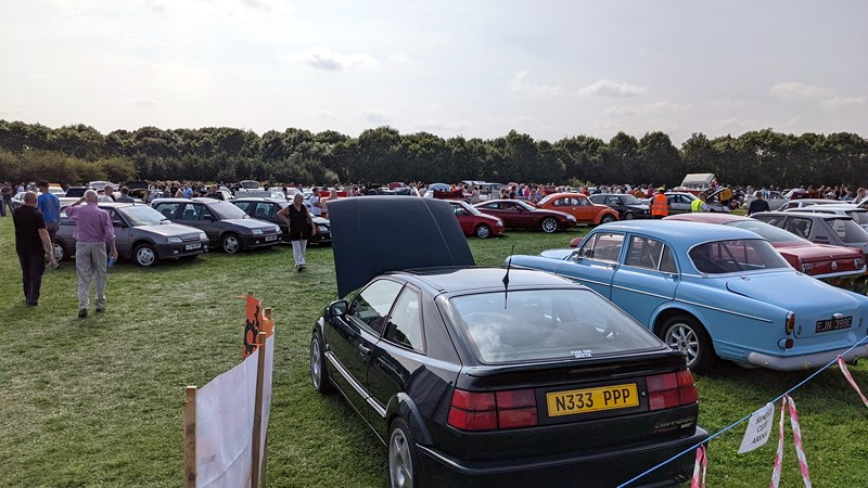 Busy with people and cars, a huge range of vehicles on show